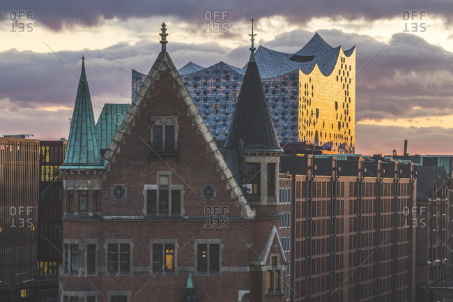 View of Elbphilharmonie and Speicherstadt against cloudy sky during sunset in Hamburg- Germany
