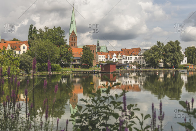 Houses and St. Aegidien-Kirche by Archenteric lake against cloudy sky in Lübeck- Germany