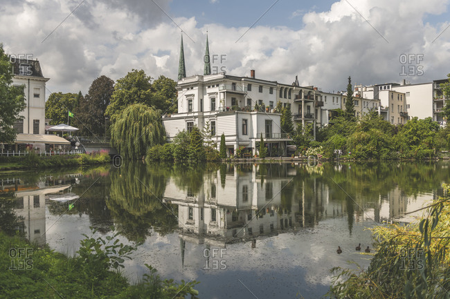 Buildings by Krihenteich lake against cloudy sky in Lübeck- Germany