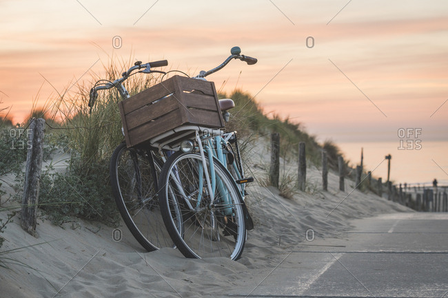 Netherlands- South Holland- Noordwijk- bicycles on sandy beach at sunset