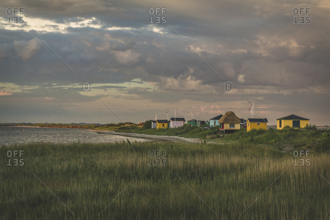 Denmark- Aeroe- Marstal- Storm clouds over traditional baths on coast