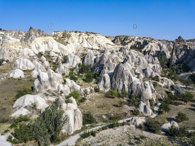Aerial view of volcanic landscape against clear blue sky during sunny day in Goreme- Cappadocia- Turkey