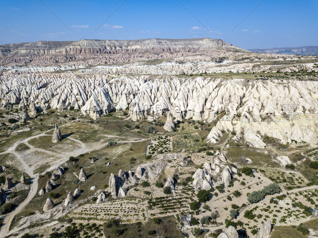 Aerial view of volcanic landscape against blue sky during sunny day at Goreme- Cappadocia- Turkey