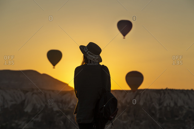 Rear view of silhouette young woman looking at hot air balloons while standing on land at Goreme- Cappadocia- Turkey