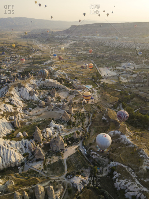 Aerial view of colorful hot air balloons flying over land at Goreme National Park- Cappadocia- Turkey