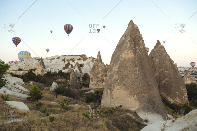 Hot air balloons flying over rocky landscape against clear sky- Cappadocia- Turkey