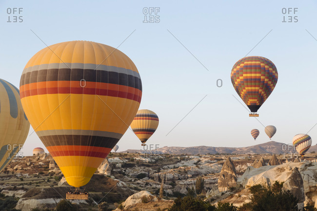 Colorful hot air balloons flying over rocky landscape against clear sky in Cappadocia- Turkey