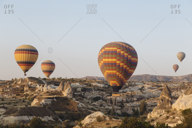 Colorful hot air balloons flying over landscape against clear sky at Cappadocia- Turkey