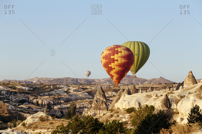 Colorful hot air balloons flying over rocky landscape against clear sky at Cappadocia- Turkey