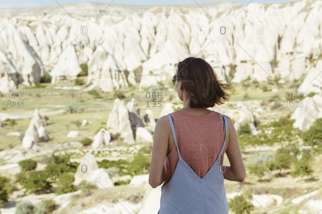 Rear view of young woman looking at rocky landscape while standing in Goreme village- Cappadocia- Turkey