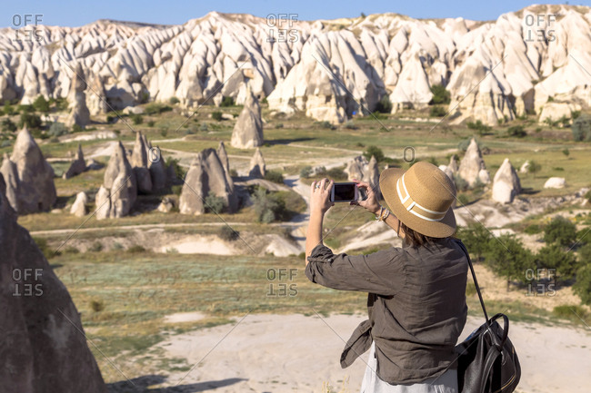 Side view of young woman photographing rocky landscape with smart phone at Goreme village- Cappadocia- Turkey