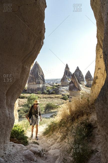 Young woman entering in cave at Goreme village- Cappadocia- Turkey