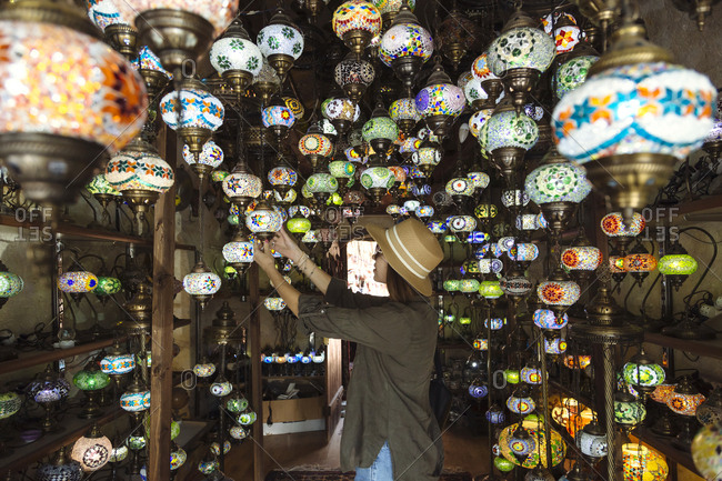 Side view of young woman wearing hat buying lanterns in store- Cappadocia- Turkey