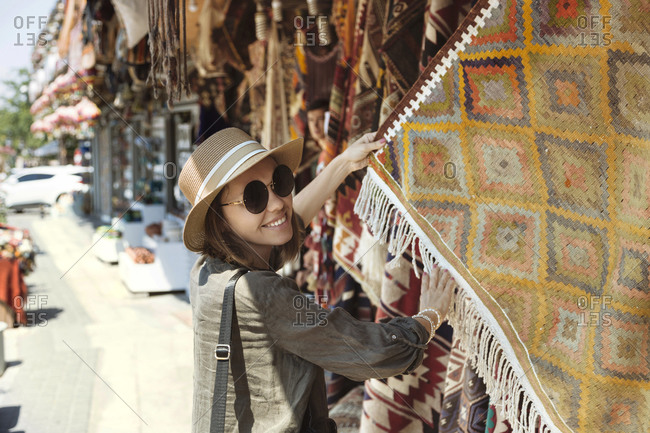Smiling young woman buying shawl at market stall in Goreme- Cappadocia- Turkey