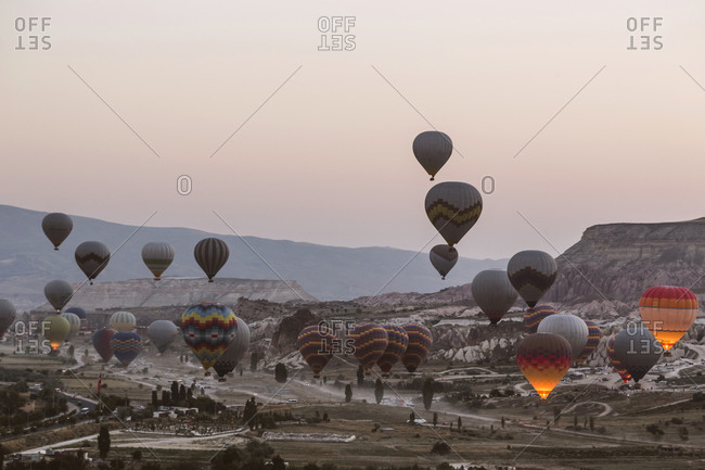 Colorful hot air balloons flying over landscape against clear sky at Goreme National Park- Cappadocia- Turkey