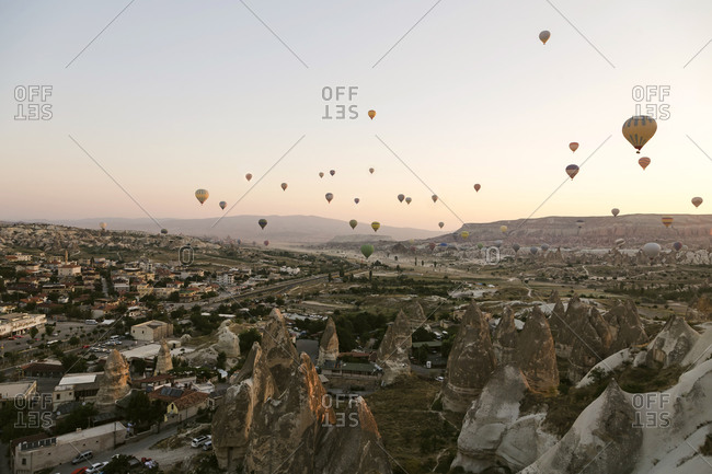 Hot air balloons flying over landscape against clear sky at Goreme National Park- Cappadocia- Turkey