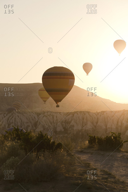 Silhouette hot air balloons flying over landscape against clear sky during sunset at Goreme National Park- Turkey