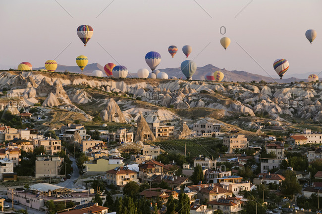 Hot air balloons flying over buildings against clear sky at Goreme National Park- Cappadocia- Turkey