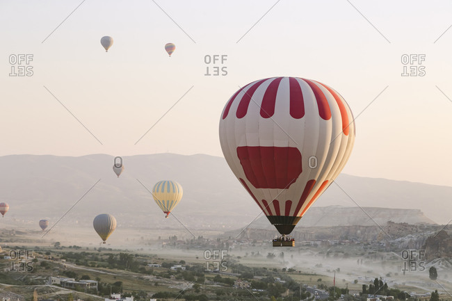 Colorful hot air balloons flying over land against clear sky at Goreme National Park- Turkey