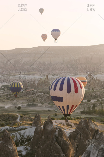 Colorful hot air balloons flying over land at Goreme National Park during sunset- Cappadocia- Turkey