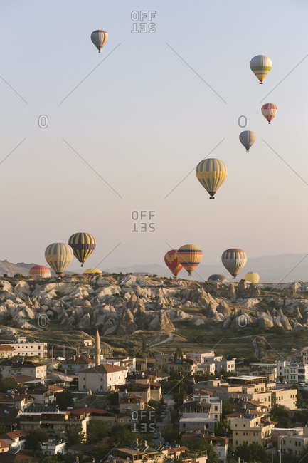 Colorful hot air balloons flying over buildings against clear sky at Goreme National Park- Cappadocia- Turkey