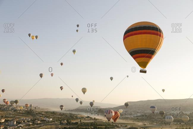 Colorful hot air balloons flying over land at Goreme National Park- Cappadocia- Turkey