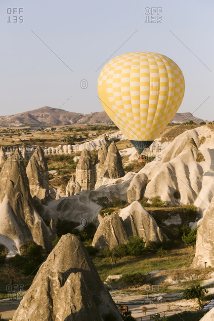 Yellow hot air balloon flying over land against clear sky at Goreme National Park- Cappadocia- Turkey