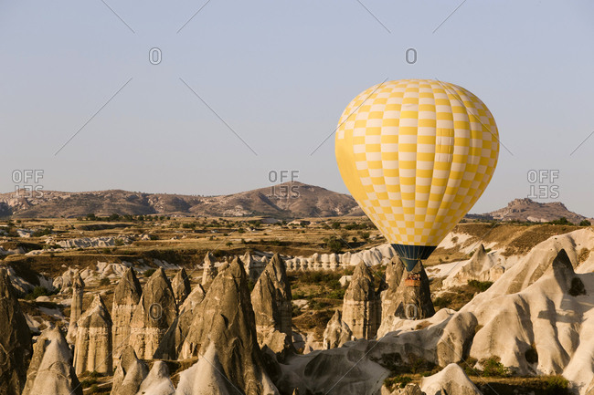 Yellow hot air balloon flying at Goreme National Park- Cappadocia- Turkey