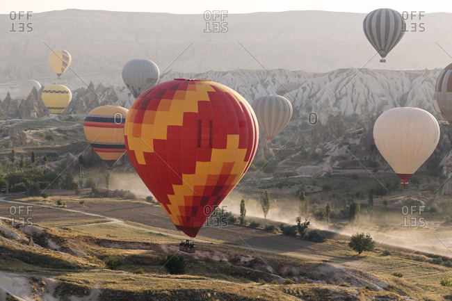 Multi colored hot air balloons flying over land at Goreme National Park during sunset- Cappadocia- Turkey