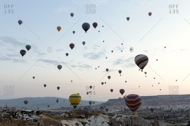Colorful hot air balloons flying over landscape against sky in Turkey during sunset- Cappadocia