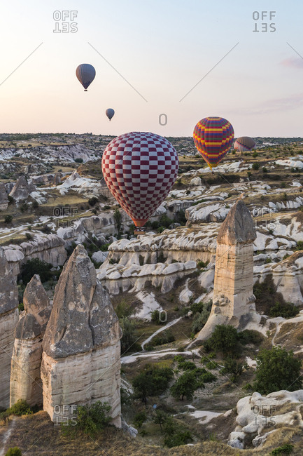 Colorful hot air balloons flying over rocky landscape against sky at sunset in Cappadocia- Turkey