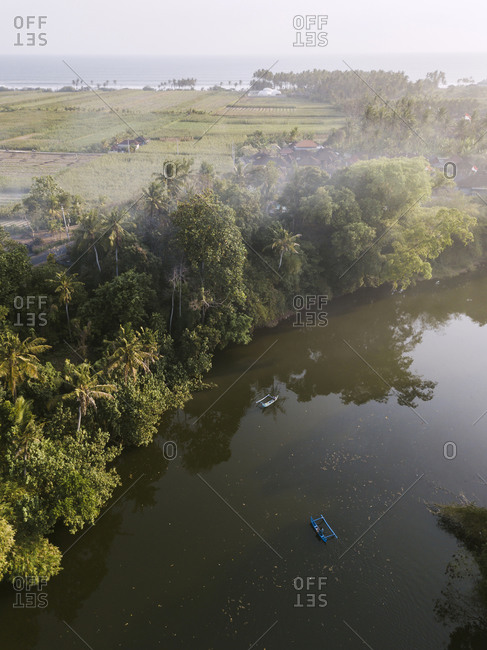 Aerial view of boats on river by land in Bali- Indonesia