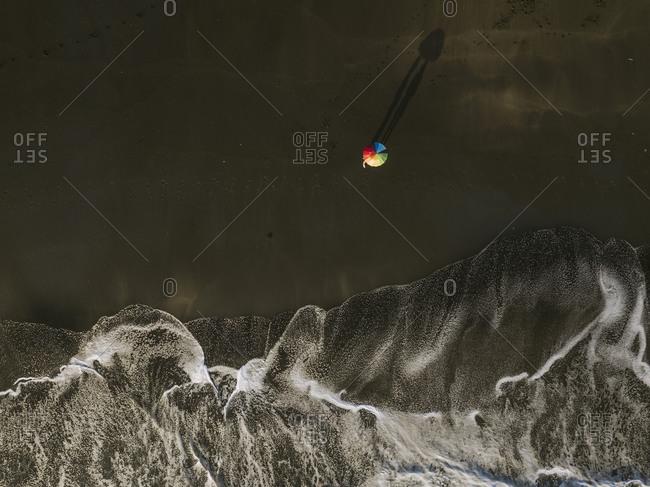 Aerial view of couple unde rainbow colors umbrella at the beach- Kedungu beach- Bali- Indonesia