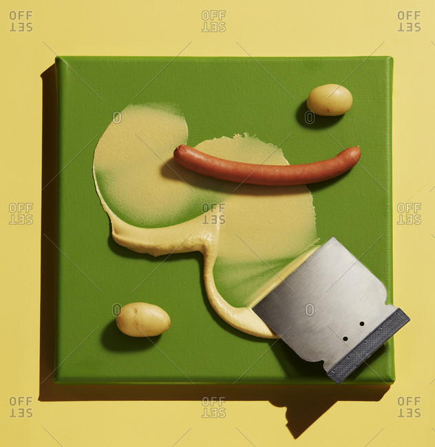 Directly above shot of potatoes with sausage and mustard sauce on yellow background