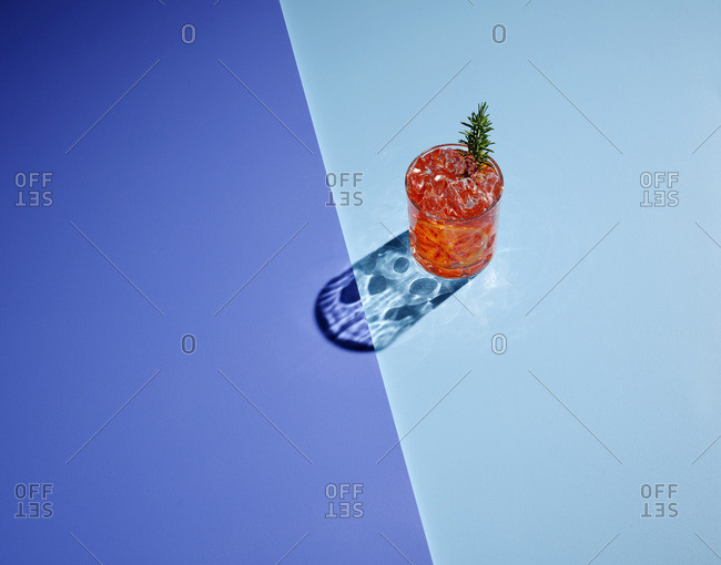 High angle view of alcohol with ice cubes on colored background