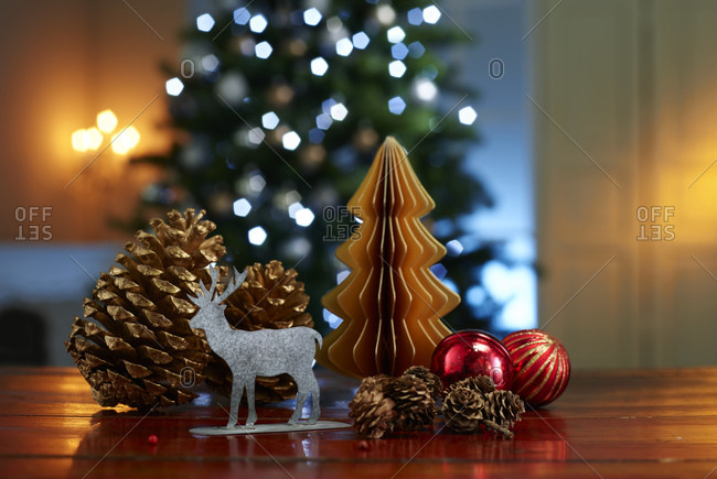 Close-up of various decorations on wooden table with illuminated Christmas tree in background at home