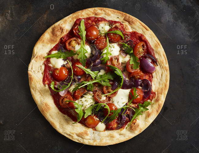Close-up of pizza with tomatoes- onions- mozzarella and basil