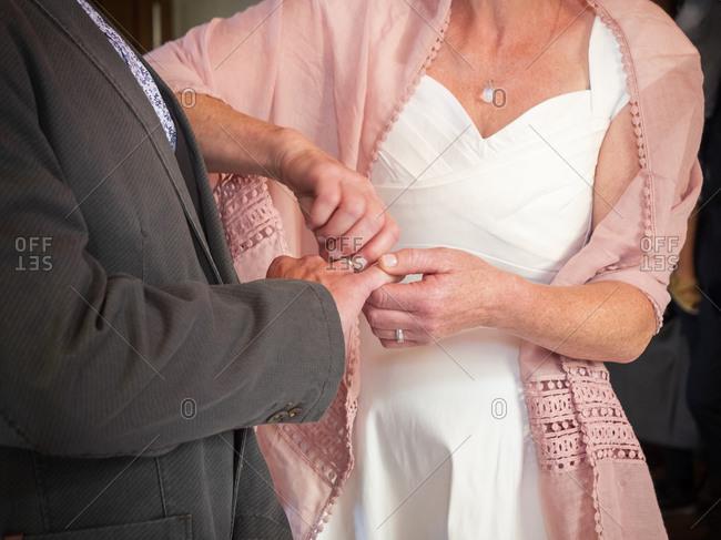 Bride putting wedding ring on finger of groom