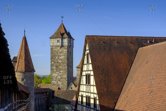 Town hall tower amidst houses against clear blue sky at Rothenburg- Germany