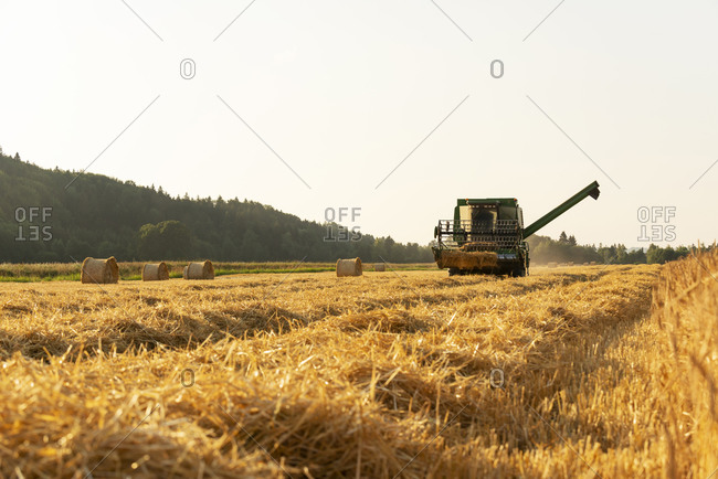 Combine harvester harvesting crops in farm against clear sky in Germany