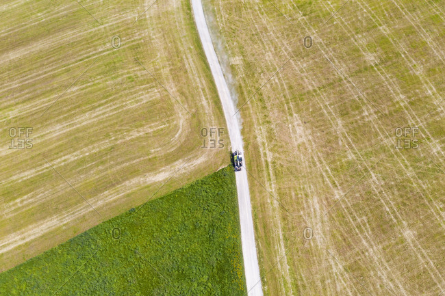 Aerial view of tractor on dirt road amidst agricultural field- Münsing- Germany