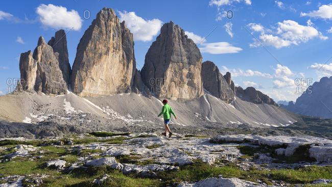 Boy walking on land against pinnacles at Tre Cime Di Lavaredo- Italy