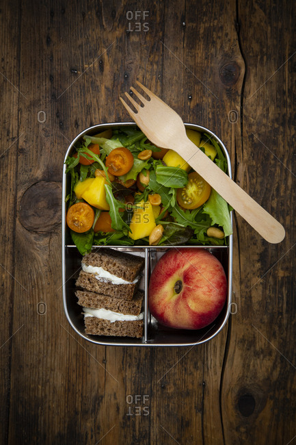 Directly above shot of vegetarian meal with fork in lunch box on wooden table