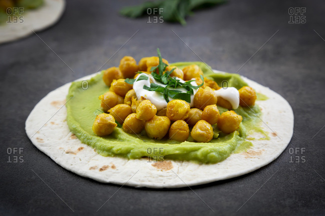Close-up of pita bread garnished with avocado cream and turmeric chickpeas on table