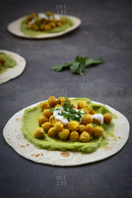 Close-up of pita bread with avocado cream and turmeric chickpeas on table