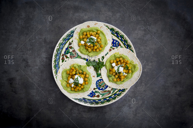 Pita bread with avocado cream and turmeric chickpeas in plate on table