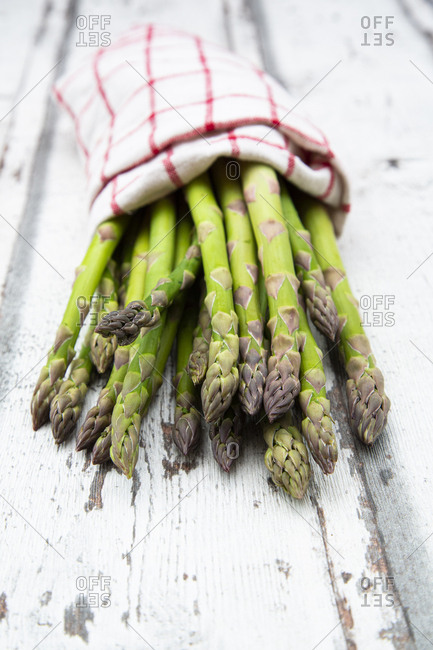 Close-up of green asparagus in napkin on wooden table