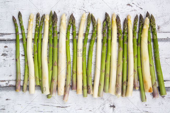 High angel view of white and green asparagus on wooden table