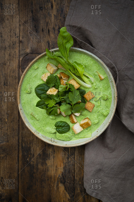 Directly above shot of green curry in bowl by napkin on table