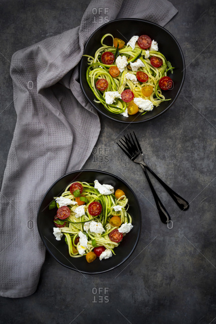 Directly above shot of vegetable salad served in bowls with forks and napkin on table